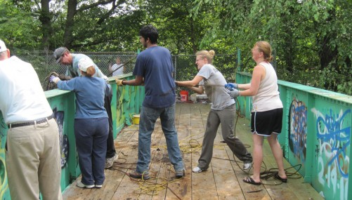 Volunteers work together to pull dumped shopping carts, bikes, and more from the river-bottom, Neponset River, Hyde Park, 2012.