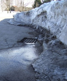 Snow-melt, picking up contaminants from a parking lot, flows into a Canton catchbasin.