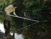 Water-sampling volunteer Trish works along Neponset River at Mattapan Square.