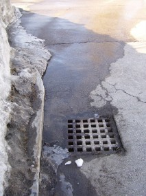 Snowmelt carries stormwater pollution into a catch basin.