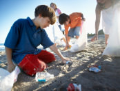 kids picking up trash from beach